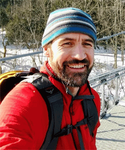 Portrait of Dennis Delay on a hike in the snow