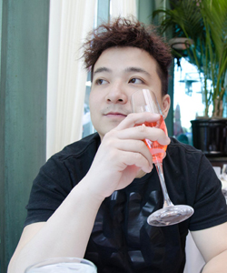 Portrait of Danny Chang sitting in a restaurant and drining a glass of wine