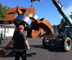 Jason Roth watches as his sculpture is moved outdoors
