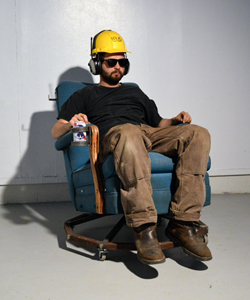 Portrait of Dane Winkler in a hard hat and ear muffs, sitting on a modified arm chair with a drink in one hand