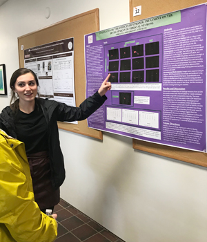 Abrianna explains a poster to visitor