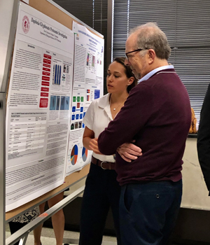Kerri discusses her poster with a judge at the competition