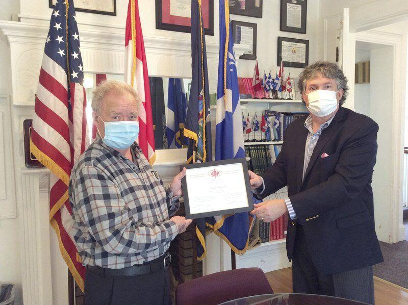 Dr. Joseph Andre Seneca accepts certificate of merit from Christopher Kirkey