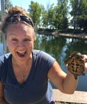 Portrait of Danielle Garneau holding up a musk turtle on the bank of Lake Champlain