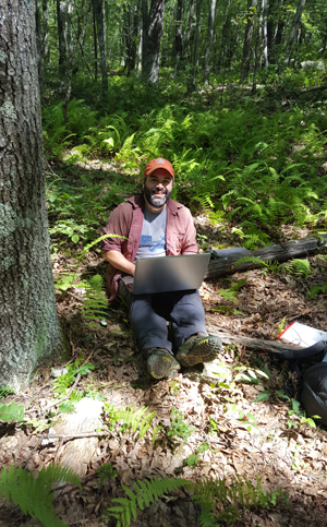 Portrait of Dr. Lesser doing research in a forest