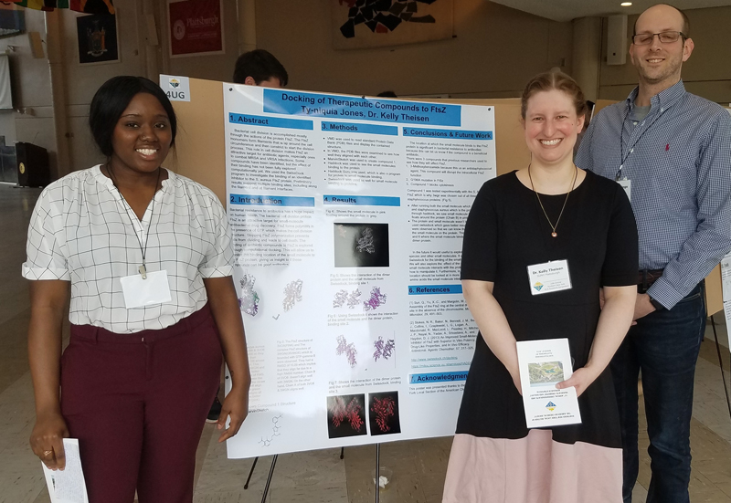 Kelly Theisen presents a poster with students at an ACS event