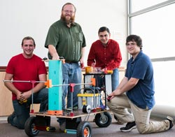 Dr. Mike Walters poses with students in the robotics club and a robot they built