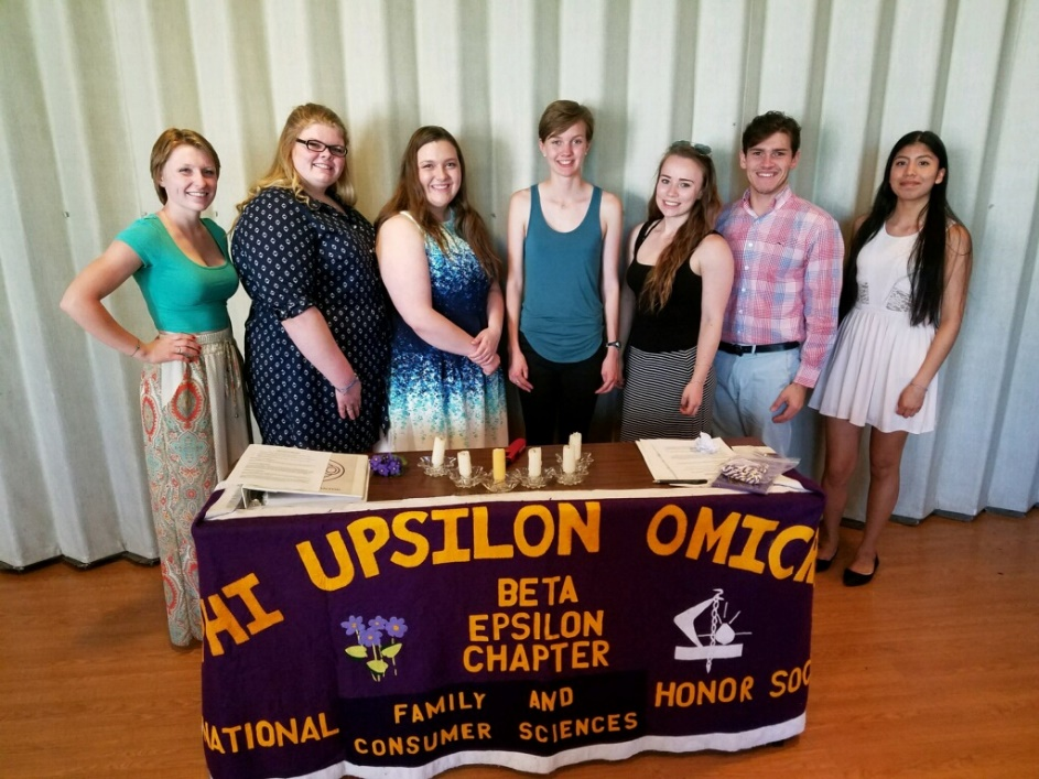 Group portrait of honor society members in front of a table display