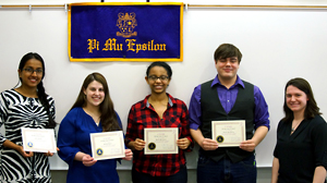 Photo of Namini De Silva, Samantha Rogers, Bezawit Woldegebriel, and Nicholas Harding holding their certificates while standing underneath the chapter banner