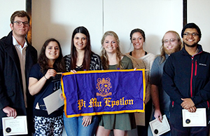 New members hold up the Alpha Xi chapter of Pi Mu Epsilon banner