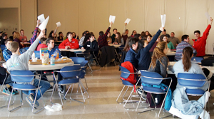 Photo of students raising their hands hoping to be called on during a round of math jeopardy