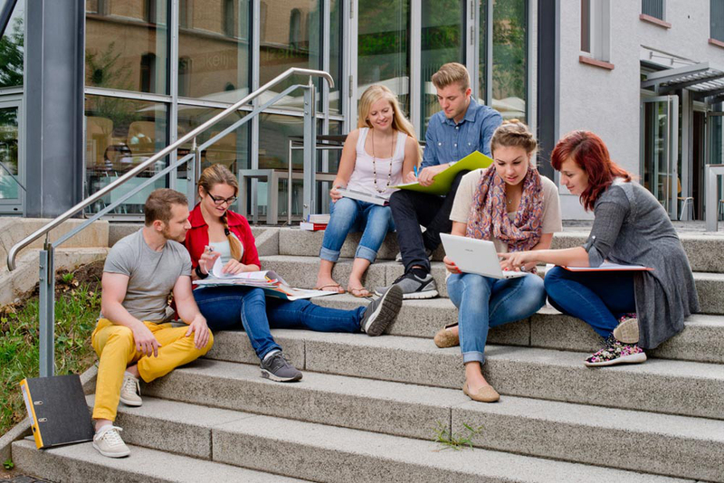 Aschaffenburg students studying together on the steps of a plaza