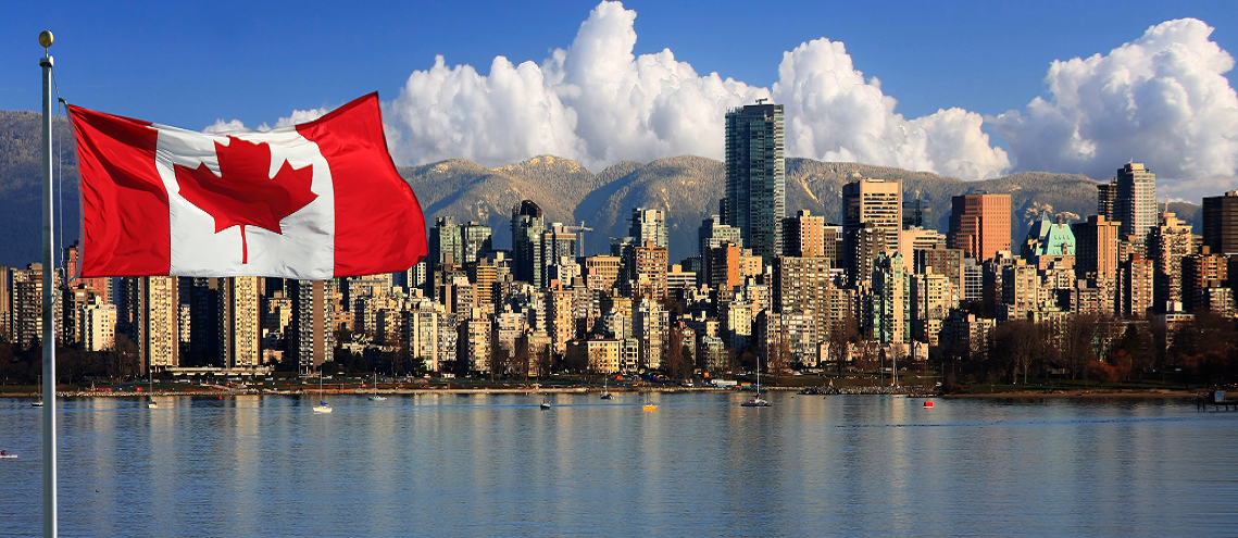 View of the Canadian flag flying in front of a Canadian city on a lake