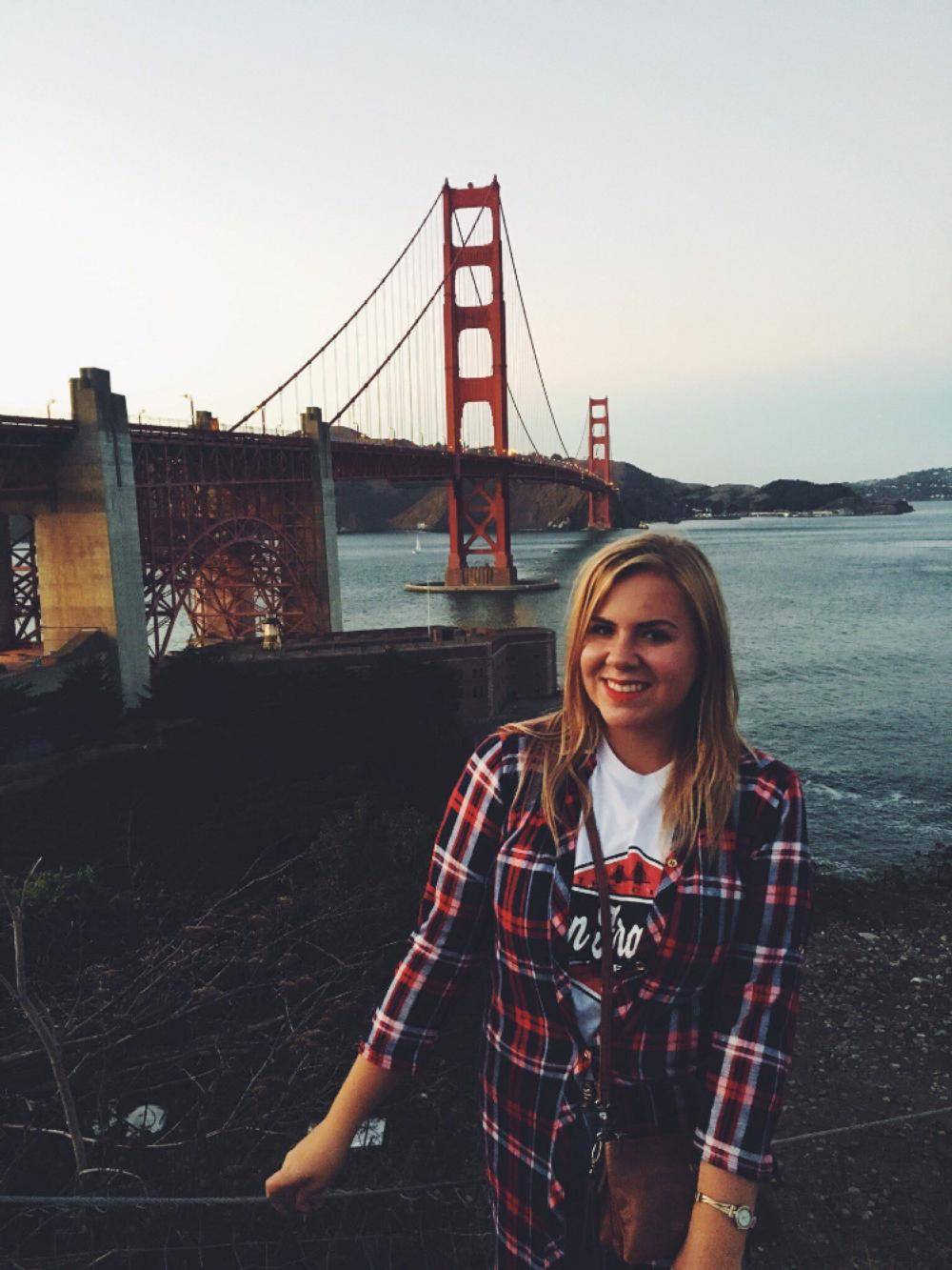 An NSE student poses in front of the Golden Gate Bridge