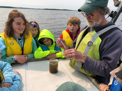 Young students on a boat on the lake learn how to do a water quality test