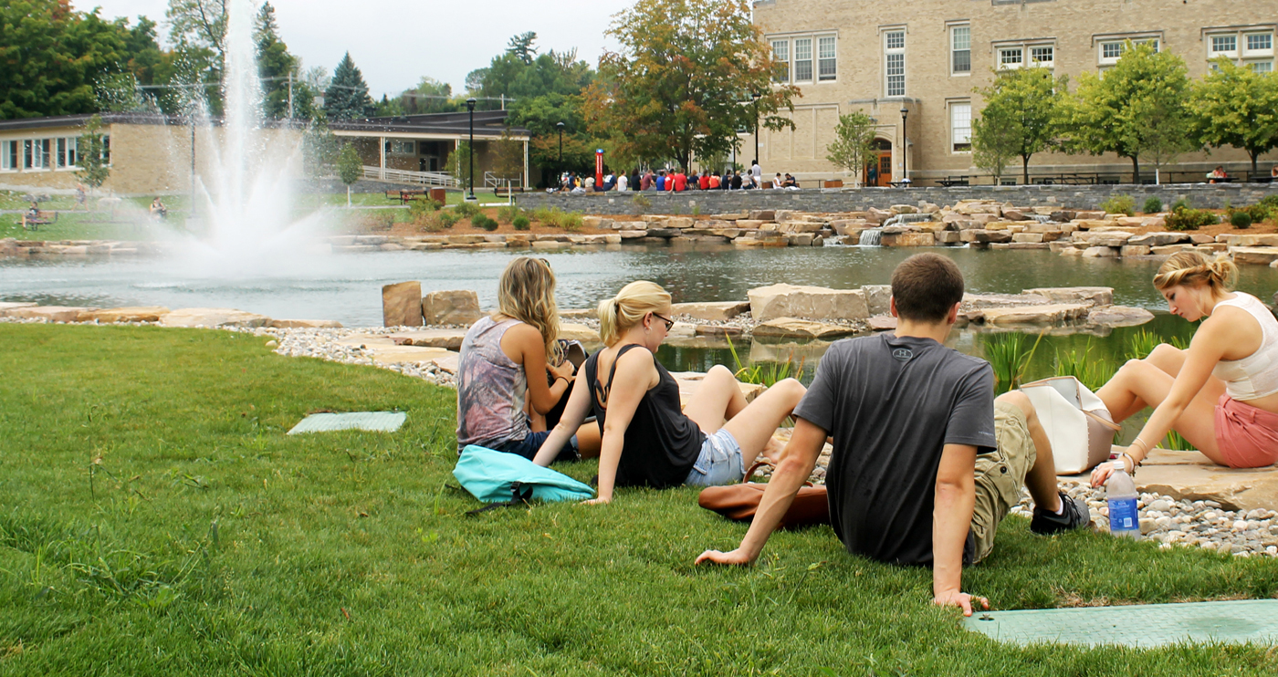 Students havign a picnic on campus in front of Hawkins Ponf