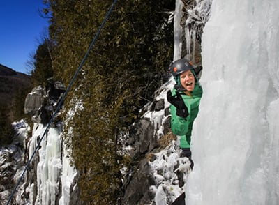 A student climbs ice on the side of a cliff