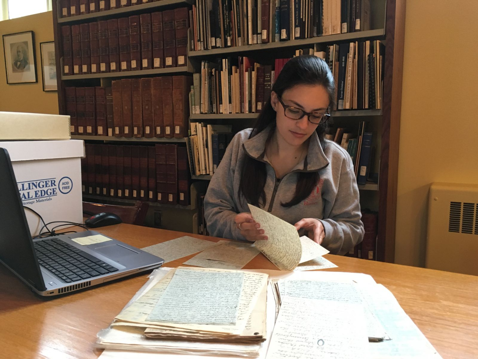 Samatha Jones looks over historic documents at Eastern Townships Resource Center in Canada