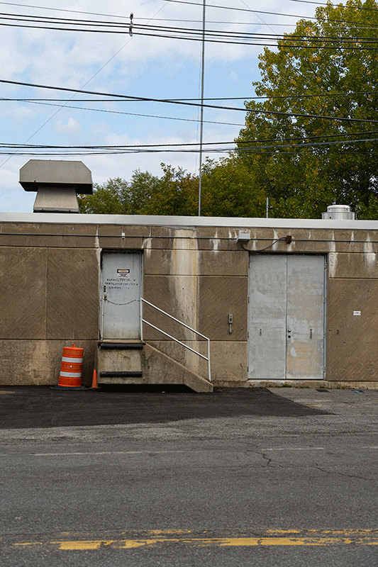 Photograph of a power station. It is light brown with a gray entry door, and a gray loading door. There is an orange safety marker on the outside.