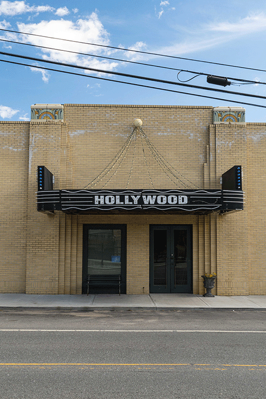 """Photograph a tan, stonework theatre with a black marque that says """"Hollywood"""" on it."""