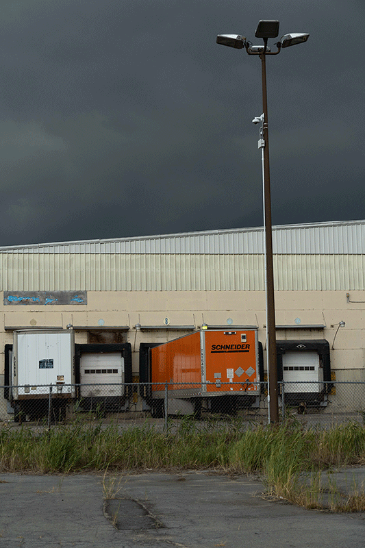 Photograph of a loading doc filled with trucks. The sky looks stormy.