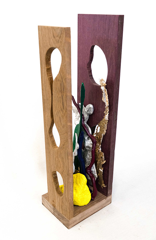 Sculpture incorporating two panels with stylistic holes in them, and some glittery, plant-like shapes in the center.