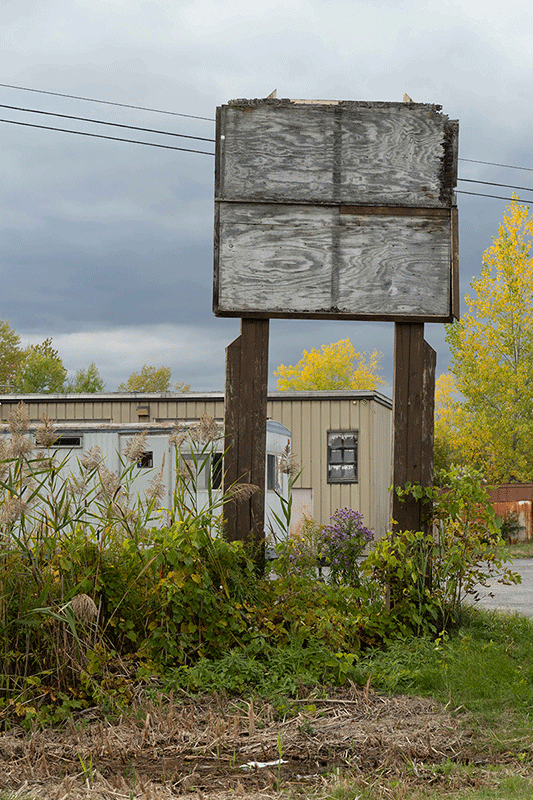 Photograph of an empty sign holder with some overgrowth. A trailer and building can be seen behind it.