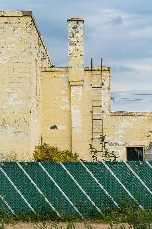 Photograph of a yellow factory. The foreground has a chain link fence with green privacy strips.