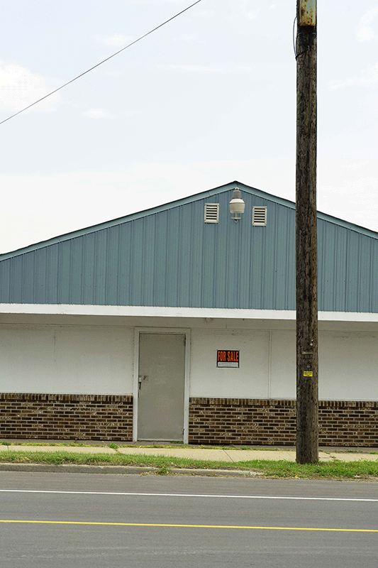 Photograph of a building that's for sale. It's white with faux brick a the bottom and a green roof. There's a utility pole in front of it.