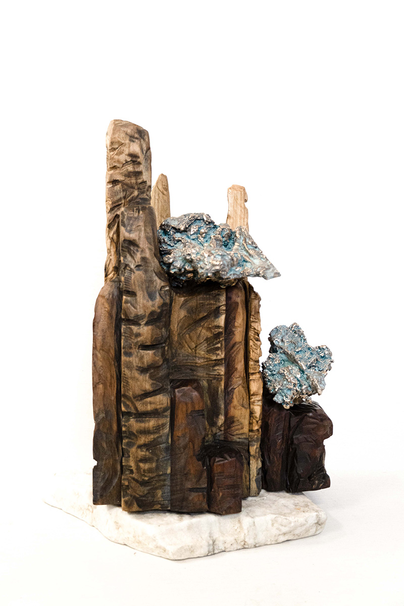 Stylistic pieces of wood with crumpled metal a top them.