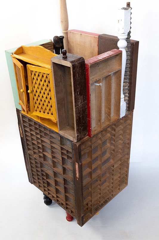 Sculpture incorporating cabinets, some table legs, castors, and crate pieces.