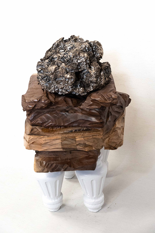 Sculpture incorporating table legs, some wrapped pieces, and a crumpled object at the top.
