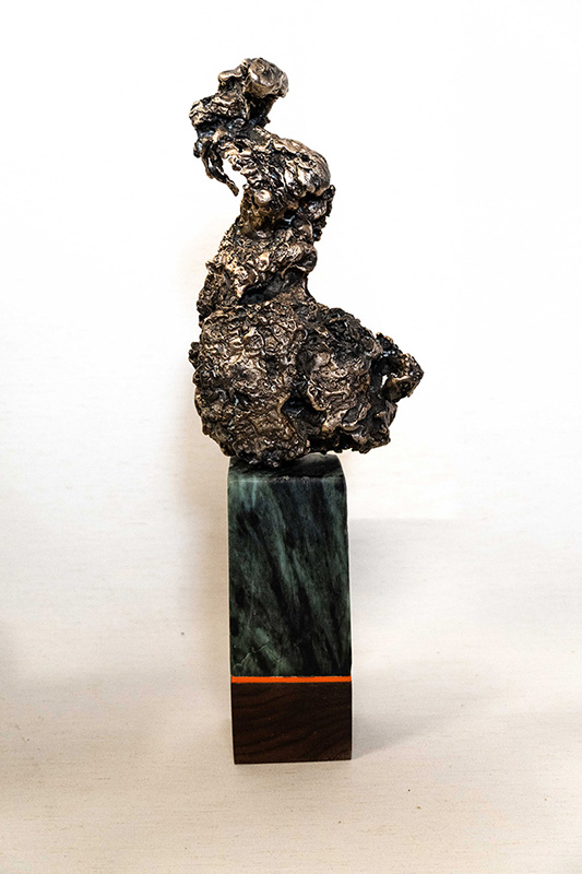 Sculpture incorporating a crumbled material shaped into a form sitting on a marble base with a black bottom with a red stripe.