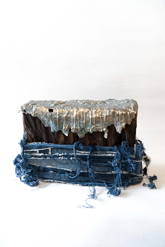 Sculpture that uses a piece of wood wrapped in jean material, and with a metal cap that looks like its melting.
