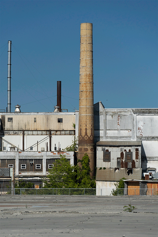 Photograph of a worn factory with a tall smokestack.