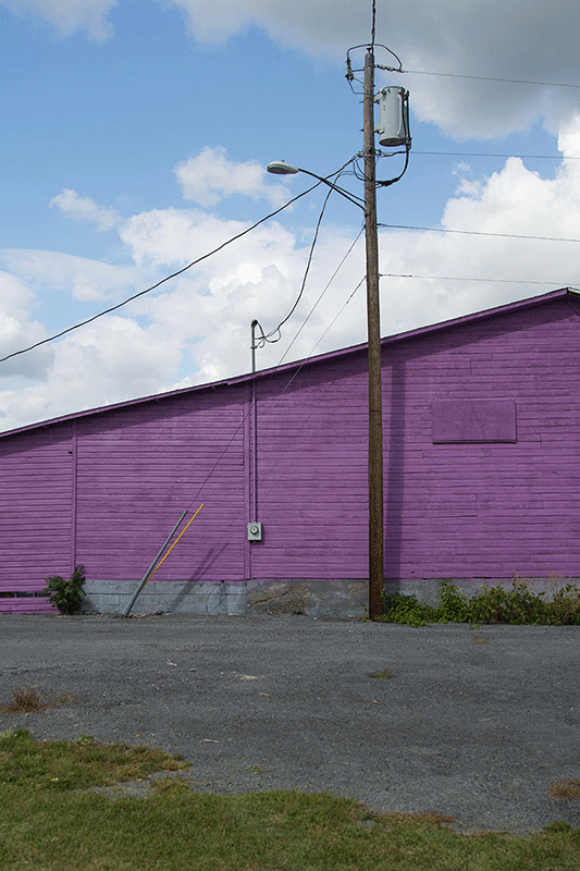 Photograph of a purple wall with a utility pole next to it. The wall has a gentle slope.