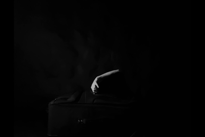 Black and white film depicting a woman interacting with a suit case.