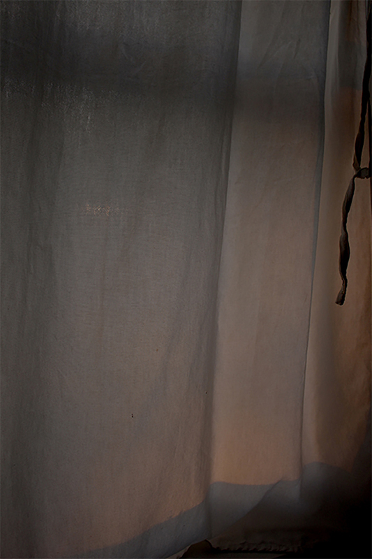 Photo of drapes on a window depicting a slight bit of natural light.