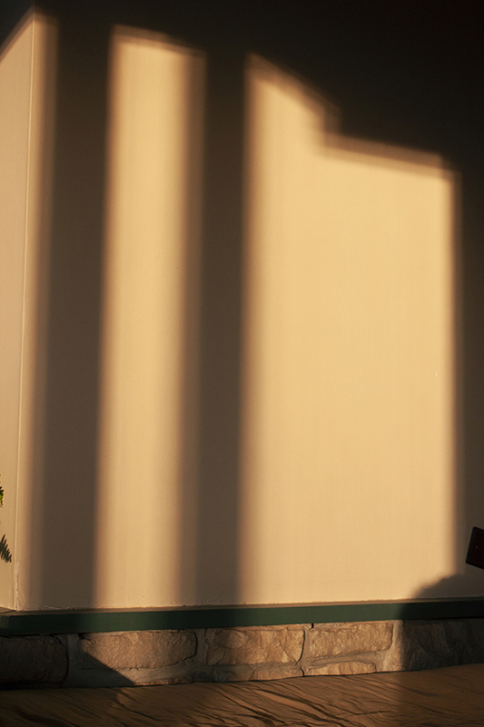 Photo of natural light against wall. There is the shadow of two lines on it.
