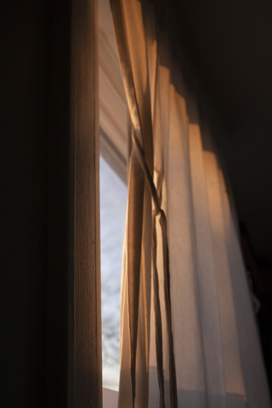 Photo of drapes on a window revealing a window with a slight bit of natural light.