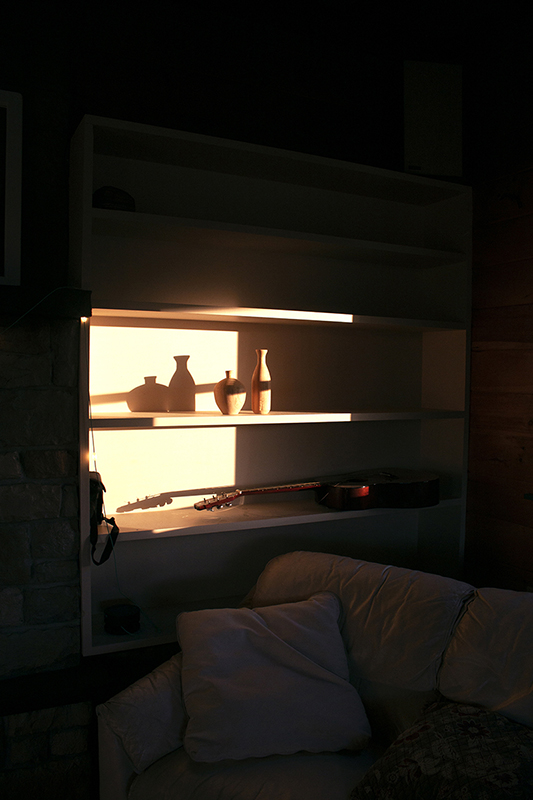 Photo of a naturally lit shelves with vases and a guitar on them.