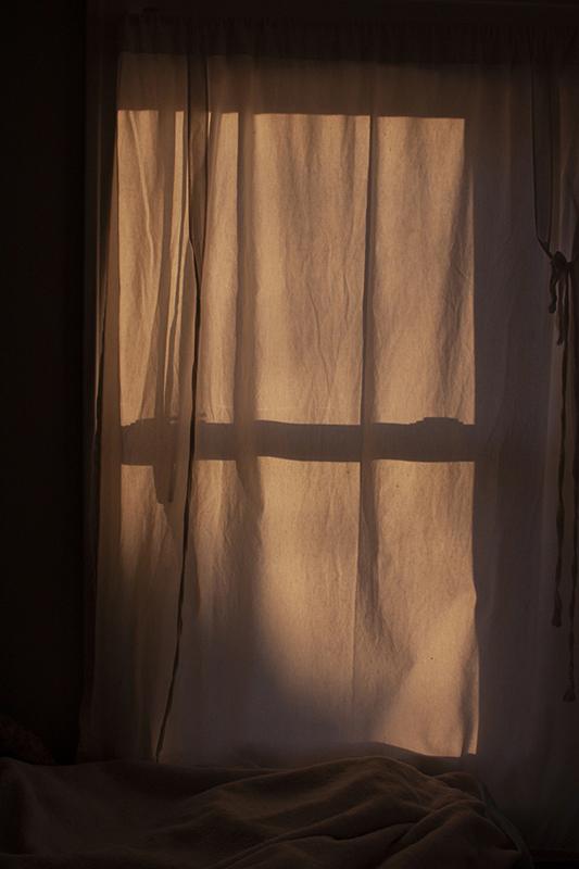 Photo of drapes on a window depicting a slight bit of orange natural light.