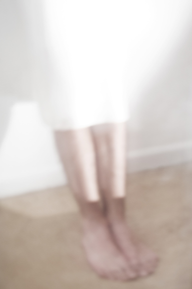 Blurry image of bare feet and shins on wood floor while wearing a white skirt.