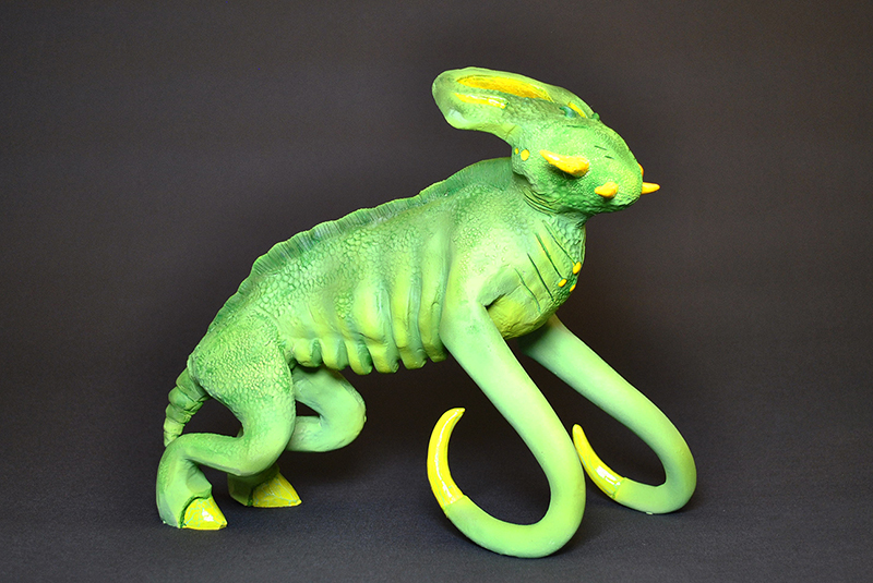 A green creature with two legs, tendrils, and an elongated head.
