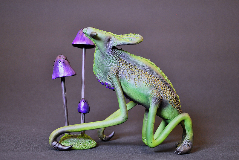 A green creature with two legs, tendrils, and an elongated head. There are also a few purple mushrooms.