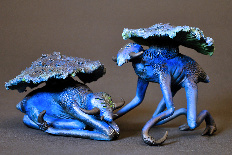 Two blue creatures with a mushroom-like shell,  two legs, tendrils, and an elongated head. One is lying down, while the other stands.