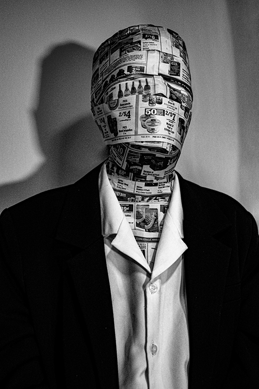 Photo of a person in a white shirt and black jacket. Their face and skin is covered with coupons.