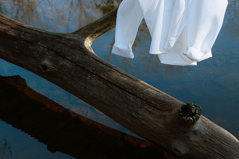 Photo of a branch in water with a white blouse hanging on it.
