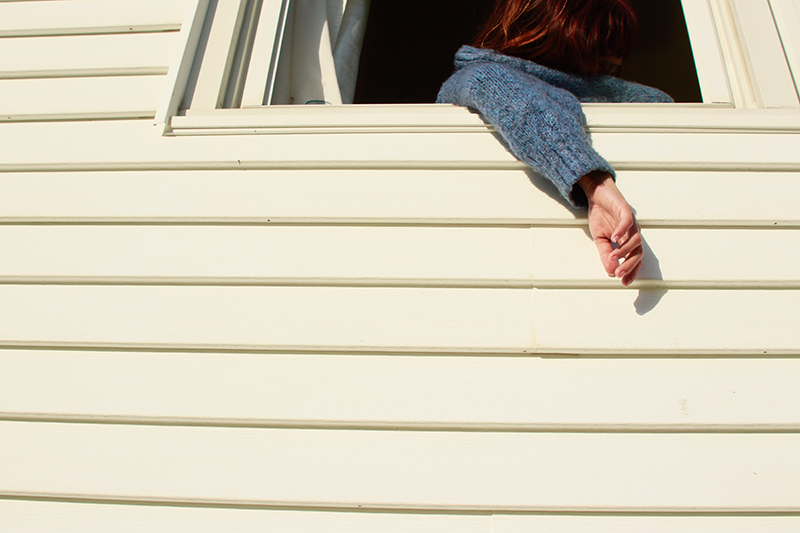 Photo of a person hanging their arm outside a white paneled house.