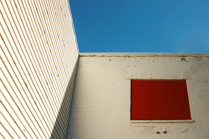 Photo of a white building with a red piece of board blocking a window.